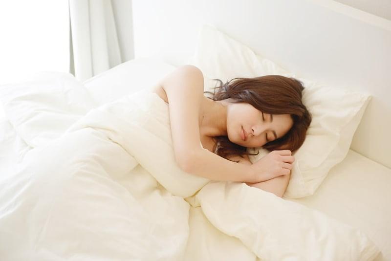 真っ白なベッドで寝る女性