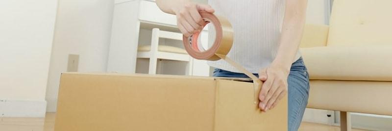 段ボールをガムテープで留める女性